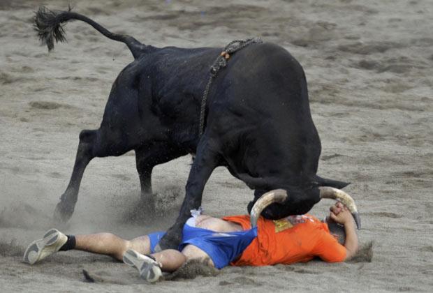 Touro deixa folião com o bumbum de fora em festival na Costa Rica (Foto: Juan Carlos Ulate/Reuters)