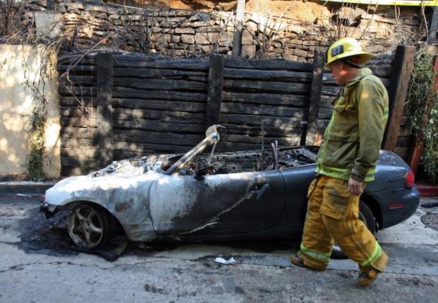 Bombeiro Dane Jackson observa carro destruído por incêndio criminoso. (Foto: Ringo H.W. Chiu/AP)