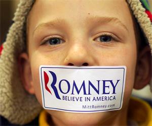 Menino de Iowa cola adesivo do pré-candidato republicano Mitt Romney na boca (Foto: Reuters)