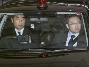 Makoto Hirata esconde o rosto no banco traseiro de um carro da polícia, enquanto de delegacia em Tóquio. (Foto: Kyodo News / AP Photo)