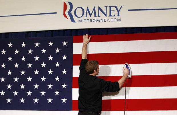 Membro da equipe de Mitt Romney passa bandeira dos EUA com ferro antes de comício. (Foto: Charles Dharapak/AP)