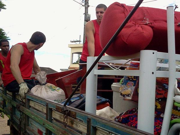 Bombeiros ajudam moradores de Três Vendas, em Campos, a encher caminhões com móveis. (Foto: Lilian Quaino/G1)