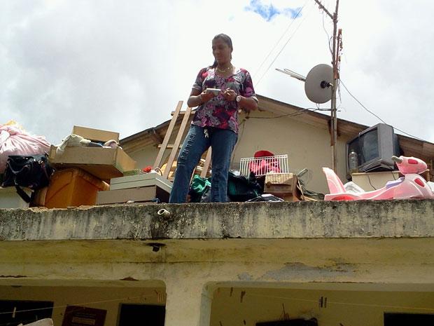 Moradora de Três Vendas, em Campos, no Norte do RJ, colocou todos os pertences no teto da casa (Foto: Lilian Quaino/G1)