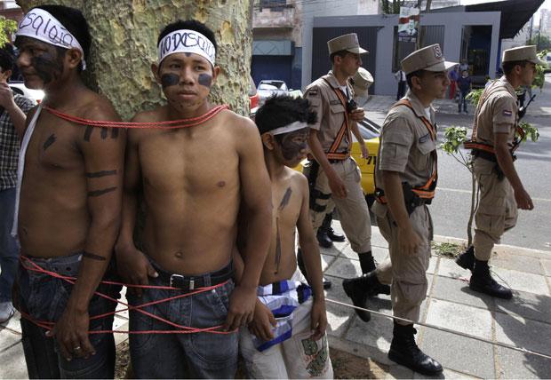 Jovens indígenas se amarraram para exigir o direito de permanecer no local (Foto: Jorge Saenz/AP)