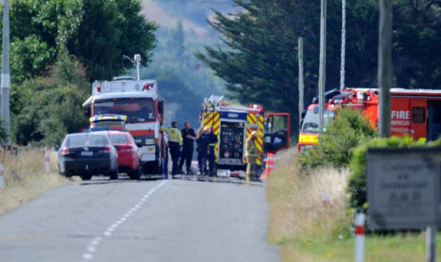 Policias e bombeiros fazem cordão de isolamento em área onde balão caiu em Carterton, na Nova Zelândia, matando o piloto e dez passageiros (Foto: AP)