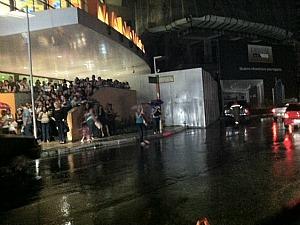 População tenta se proteger da chuva em frente à shopping da Zona Centro-Sul (Foto: Muniz Neto/G1 AM)