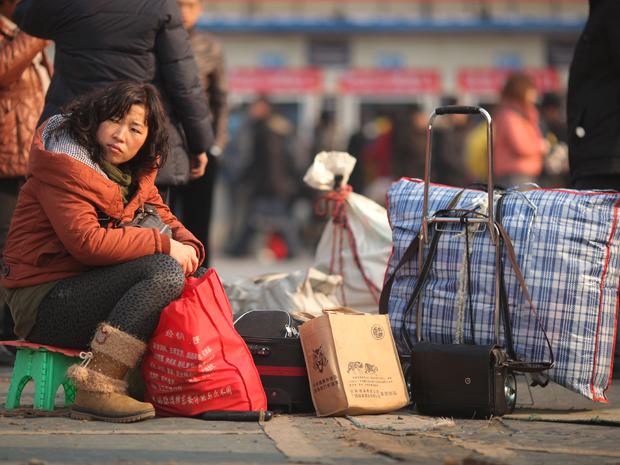 Mulher senta em cima de bagagem à espera de trem em estação de Pequim (Foto: AFP)