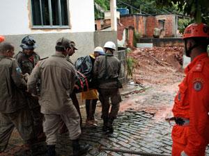 Corpo carregado pelos bombeiros após deslizamento em Jamapará (Foto: Marcelo Piu/ Ag. O Globo)