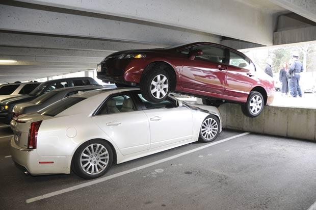 Motorista pisou no acelerador em vez do freio e estacionou em cima de outro veículo. (Foto: Wellesley Police Department/AP)