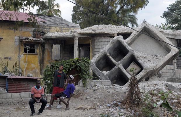 Moradores sentam em frente a casa destruída no terremoto, em foto de 3 de janeiro deste ano (Foto: Swoan Parker/Reuters)