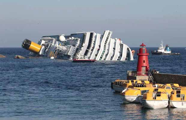 Navio parcialmente submerso após o acidente é visto na manhã deste sábado (14) próximo á ilha de Giglio, na costa da Toscana (Foto: AP)