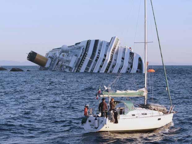 Barco passa em frente do Costa Concórdia na manhã deste domingo (15) (Foto: AP)