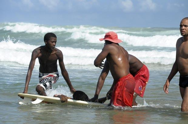 Banhistas socorrem o homem de 25 anos atacado por um tubarão na Second Beach, na costa da África do Sul (Foto: Roger Bulbring/Reuters)