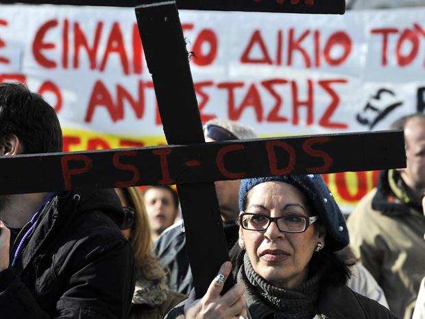 Uma funcionário do Ministério da Cultura carrega cartaz durante protesto em Atenas (Foto: AFP)