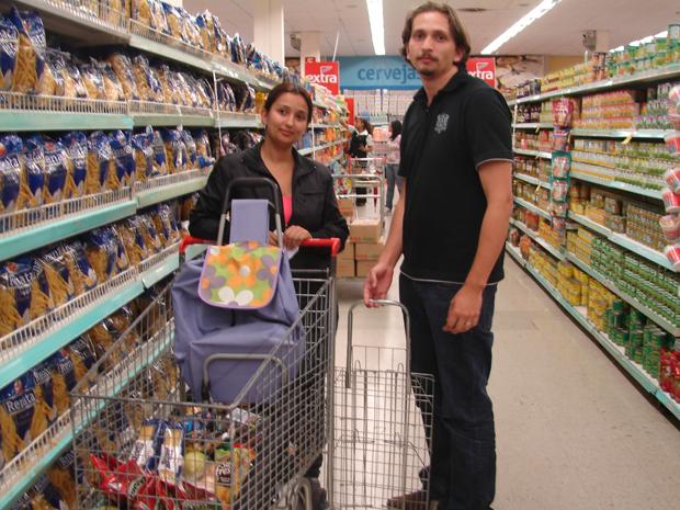 Os irmãos Mônica Teles, 27, e Tiago Teles, 23, com os carrinhos de feira e com a mochila que usaram para levar as compras do supermercado (Foto: Rafael Sampaio/G1)