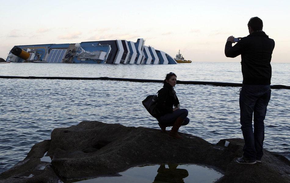 20 de janeiro - Mulher posa para foto na costa da ilha de Giglio em frente ao navio de cruzeiro naufragado