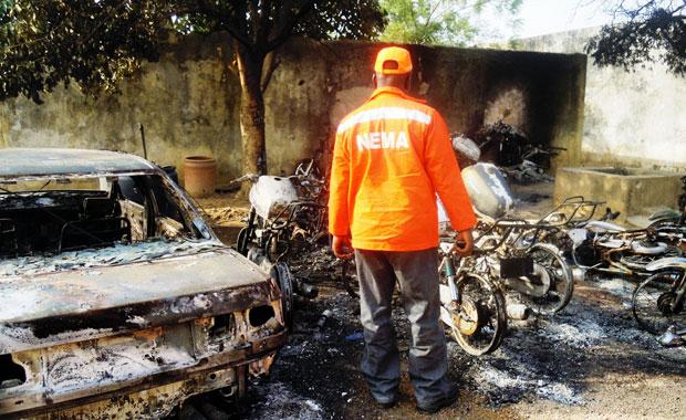 Resgatista observa destroços de carros e motos queimados em ataques no norte da cidade de Kano (Foto: Aminu Abubakar/AFP)
