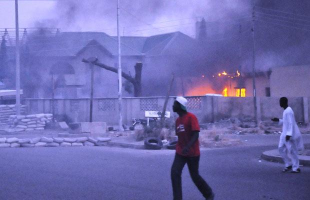 Moradores caminham perto de edifícios incendiados após ataques na última sexta, em Kano (Foto: AFP)