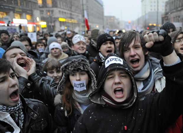 Manifestantes gritam frases contra projeto de lei antipirataria Acta. O protesto, realizado nesta terça-feira (24), foi feito em frente a um escritório da União Europeia na Polônia. O Acta almeja criar padrões internacionais para a proteção da propriedade intelectual, mas grupos se opõem dizendo que ele limita a liberdade da internet. A Polônia se comprometeu a assinar o acordo na próxima quinta-feira (26). (Foto: Janek Skarzynski/France Presse)