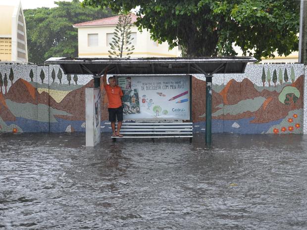 Homem sobe em banco para fugir da água da chuva na Avenida Epitácio Pessoa (Foto: Walter Paparazzo/G1)