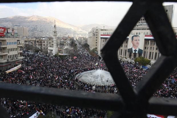 Um imenso retrato do ditador Bashar al Assad é visto durante manifestação de apoiadores do governo, em Damasco, nesta quinta (26) (Foto: Louai Beshara / AFP)
