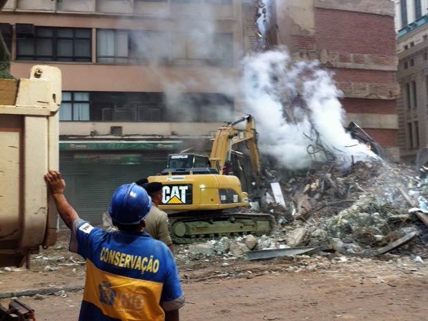 Trabalhador observa movimentação de máquinas que removem escombros (Foto: Thamine Leta/G1)