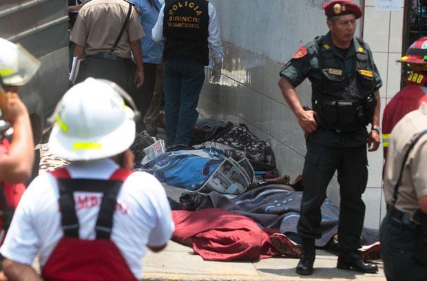 Corpos retirados do incêndio são vistos no sábado (28) entre oficiais que trabalham no local, em Lima (Foto: Reuters/Andina)