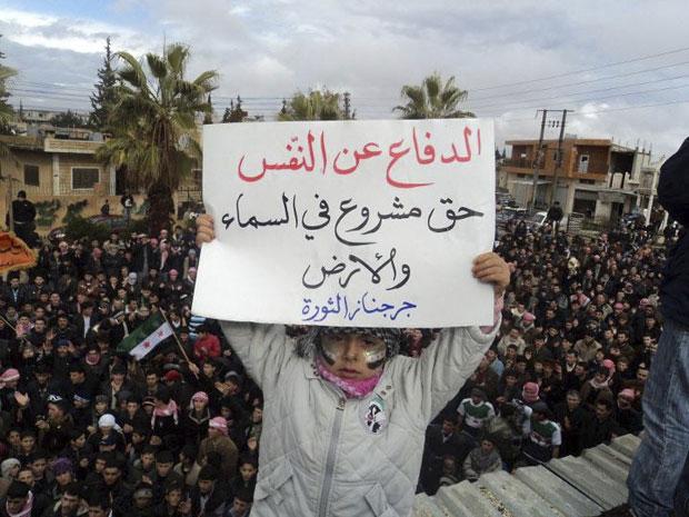 Menina síria ergue cartaz que diz 'Legítima defesa é um direito' em protesto perto de Idlib na sexta (27), em foto divulgada neste domingo (29) (Foto: Reuters)