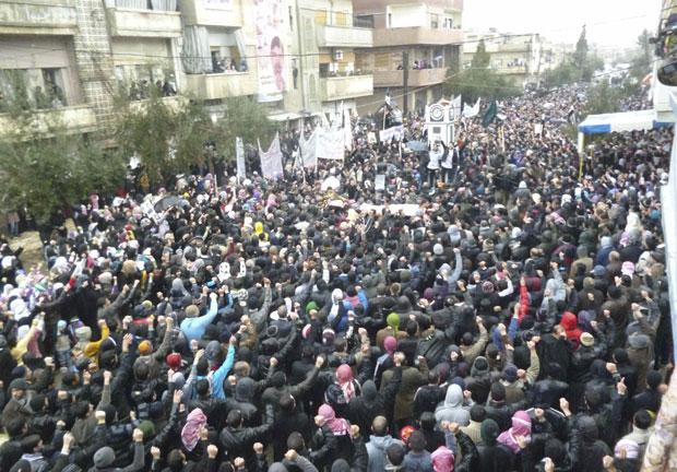 Pessoas contrárias ao regime sírio erguem caixão durante enterro de manifestante que teria sido morto por forças do governo, em Baba Amro, perto de Homs (Foto: Reuters)