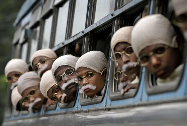 Já vestidas de Gandhi, crianças indianas chegam de ônibus ao local do evento (Foto: Bikas Das/AP)
