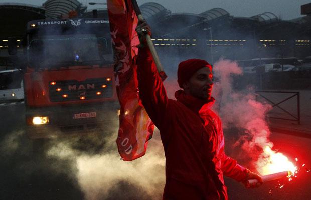 Trabalhador bloqueia rua próximo à estação de trem de Midi-Zuid, em Bruxelas nesta segunda (Foto: Yves Herman/Reuters)