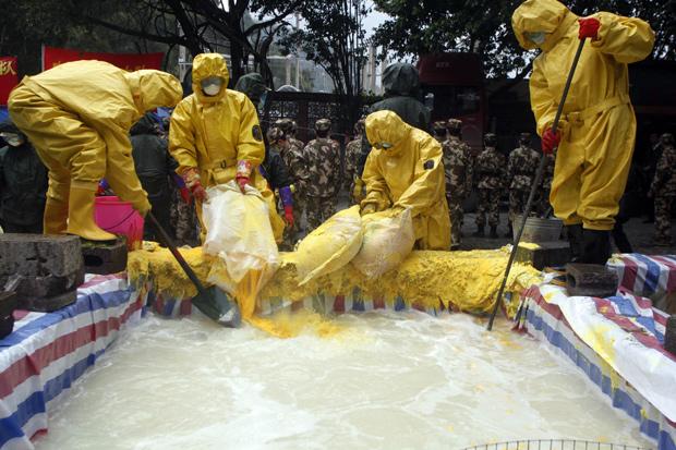 Policiais chineses usam roupas especiais para tentar controlar a poluição por cádmio. (Foto: AP Photo)