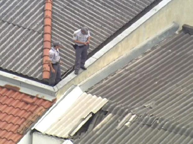 PMs procuram criminoso no telhado da agência (Foto: Reprodução/TV Globo)