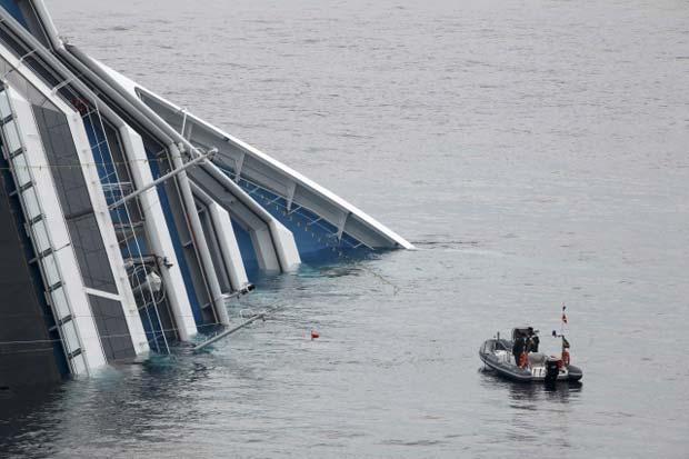 Barco da Guarda Costeira passa diante do Costa Concordia nesta terça-feira (31) (Foto: Reuters)