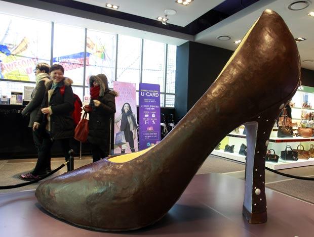 Sapato de salto gigante está exposto em frente a uma loja de departamentos em Seul. (Foto: Lee Jin-man/AP)