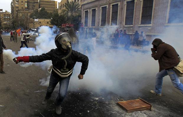 Manifestante com máscara de gás se prepara para jogar de volta uma granada de gás lacrimogêneo contra policiais perto do Ministério do Interior, no Cairo (Foto: Mahmud Hams/AFP)