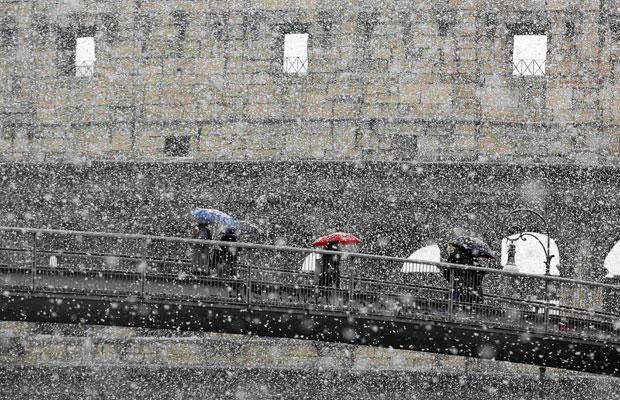 Pessoas se protegem sob guarda-chuvas em frente ao Coliseu romano, nesta sexta (Foto: Alessandro Bianchi/Reuters)