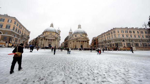 Pessoas andam em praça do Pappolo, em Roma, no segundo dia de neve em 15 anos (Foto: Tiziana Fabi / AFP)