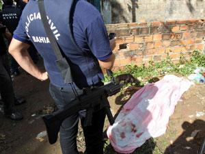 Policiais civis observam o corpo de uma jovem que foi encontrada com marcas de tiro no bairro de São Marcos (Foto: Lúcio Távora/Agência A Tarde/AE)