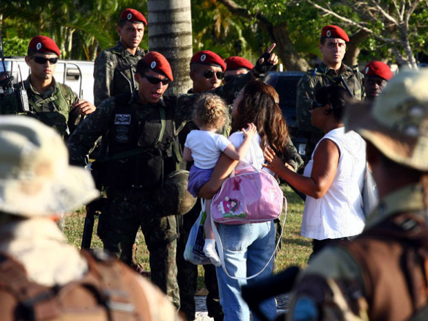 Mulher tenta passar por homens do Exército com uma criança no colo durante manifestação de policiais militares na Assembleia Legislativa, em Salvador (Foto: Lúcio Távora/Agência A Tarde/AE)