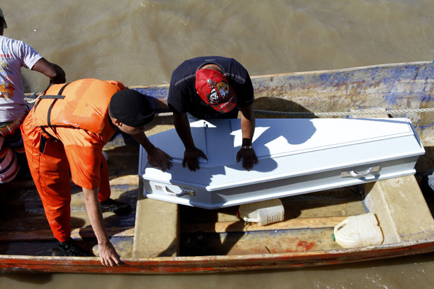Familiar acompanha de barco o transporte de um caixão com o corpo de uma das vítimas do naufrágio na República Dominicana, no domingo (5) (Foto: AP)