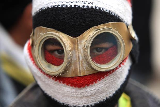 Manifestante mascarado durante protesto contra a junta militar egípcia nesta segunda-feira (6) no Cairo (Foto: AP)