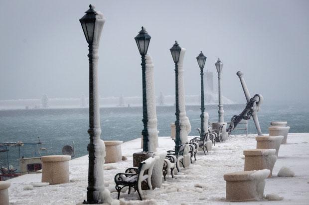 Vento fez com que o gelo se acumulasse mais em um lado dos postes (Foto: Darko Bandic/AP)