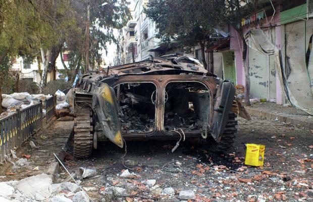 Veículo militar é destruído após confrontos entre forças oficiais e opositoras em Homs, no último dia 4 (Foto: Reuters)