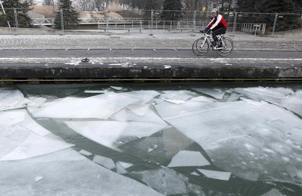 Ciclistas passam pelo canal de La Villette, congelado, nesta quinta-feira (9) em Paris (Foto: Reuters)