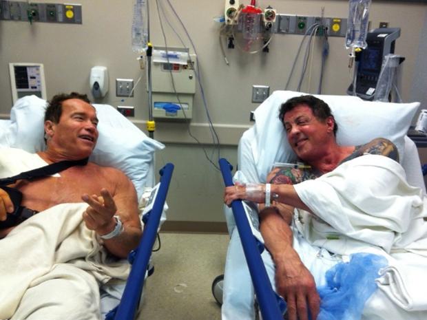 """Schwarzenegger publicou em seu Twitter foto ao lado de Stallone em hospital. """"Depois de toda a ação, acrobacias e abuso físico em 'Os mercenários 2', era hora de tratar o ombro. Olha quem estava coincidentemente na fila atrás de mim para sua cirurgia no ombro. Agora estamos prontos para outra rodada de grandes momentos de ação quando filmaremos 'The tomb' (Foto: Divulgação)"""