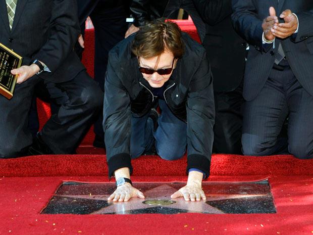 Paul McCartney se ajoelha diante da estrela cravada na calçada diante do prédio da Capitol Records, em Los Angeles. Músico foi o último beatle a receber a homenagem (Foto: Reuters)
