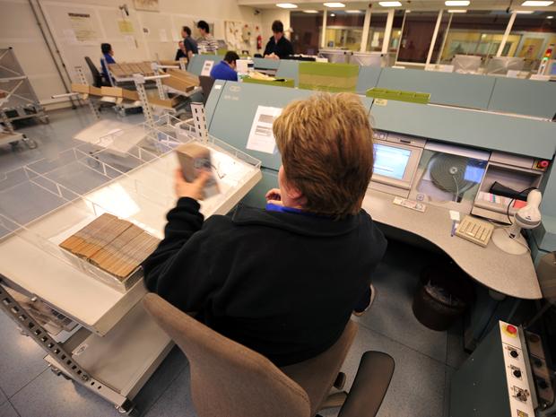 Uma emprega manipula notas em um centro de logística do Banco Central da Hungria (Foto: AFP)