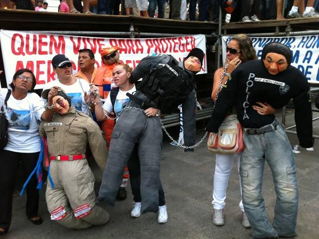 Manifestantes se acorrentam a bonecos vestidos com fardas da polícia e dos bombeiros (Foto: Carolina Lauriano/ G1)