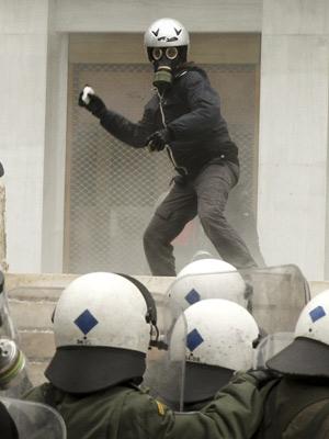 Manifestante joga pedras em policiais de choque durante confrontos em Atenas. (Foto: John Kolesidis/Reuters)